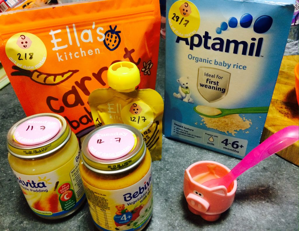 Jars and packets of baby food with the Out Of Date Mates magnets and stickers on.