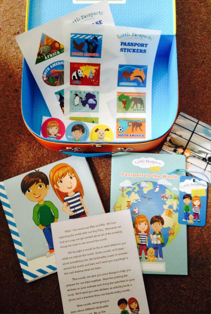 Contents of Little Passports suitcase. Stickers, passport, postcard, suitcase tag, intro