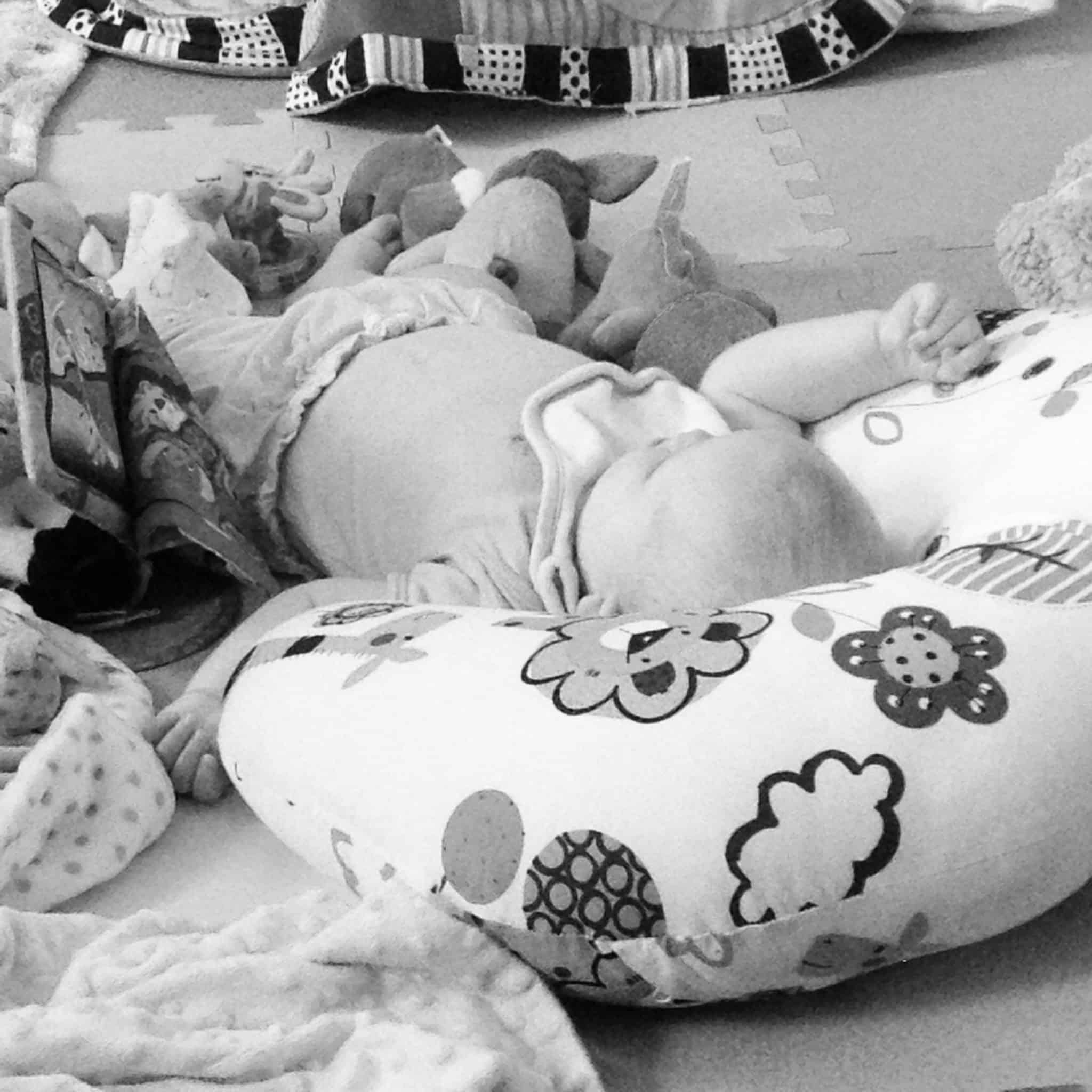 My Sunday Photo - Baby Girl at 7 Months - A black and white photo of baby girl lying on the floor with her head on her u-shaped cushion.