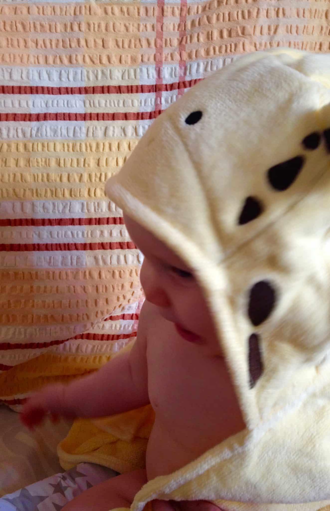 baby girl with her giraffe hooded towel on