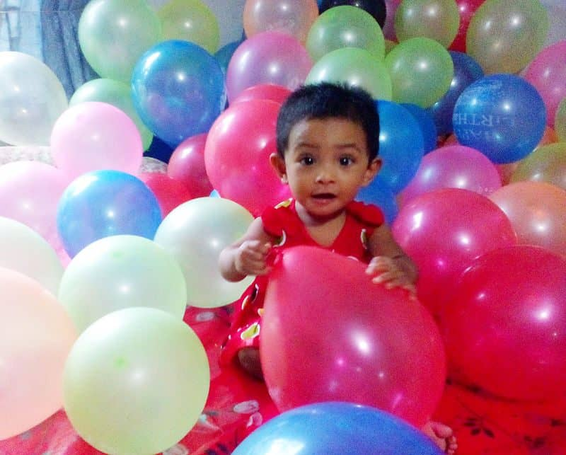 one_year_baby_is_playing_with_birthday_balloons