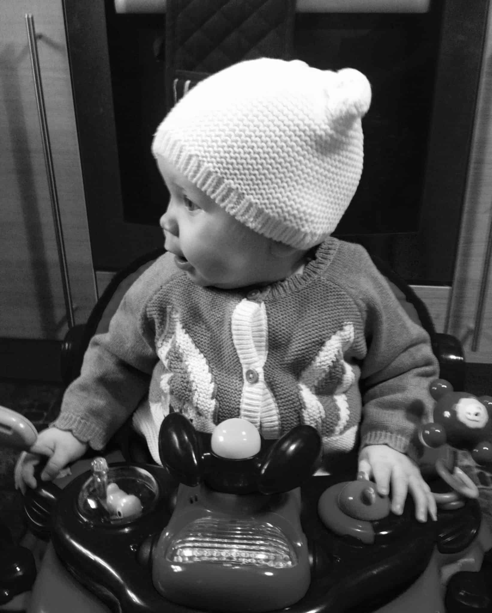 Baby girl all ready to go out with her woolly hat and cardi on