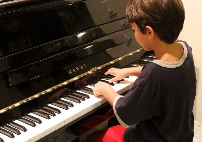 boy learning to play the piano
