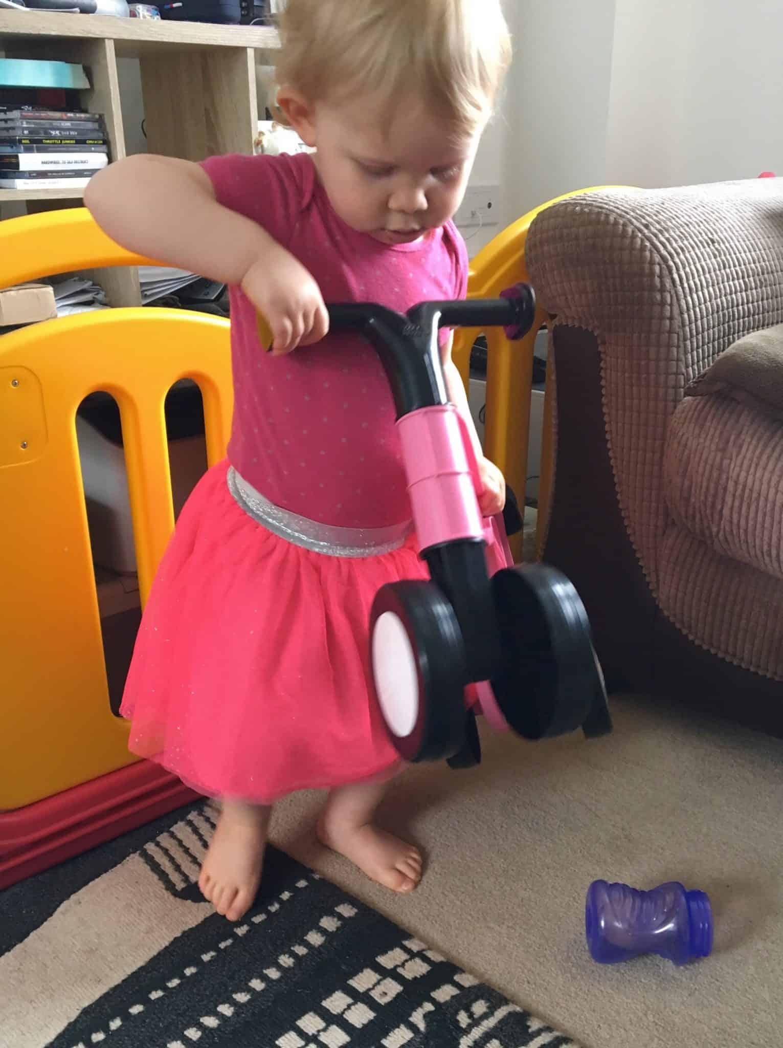 Baby girl inspecting her Toddlebike 2