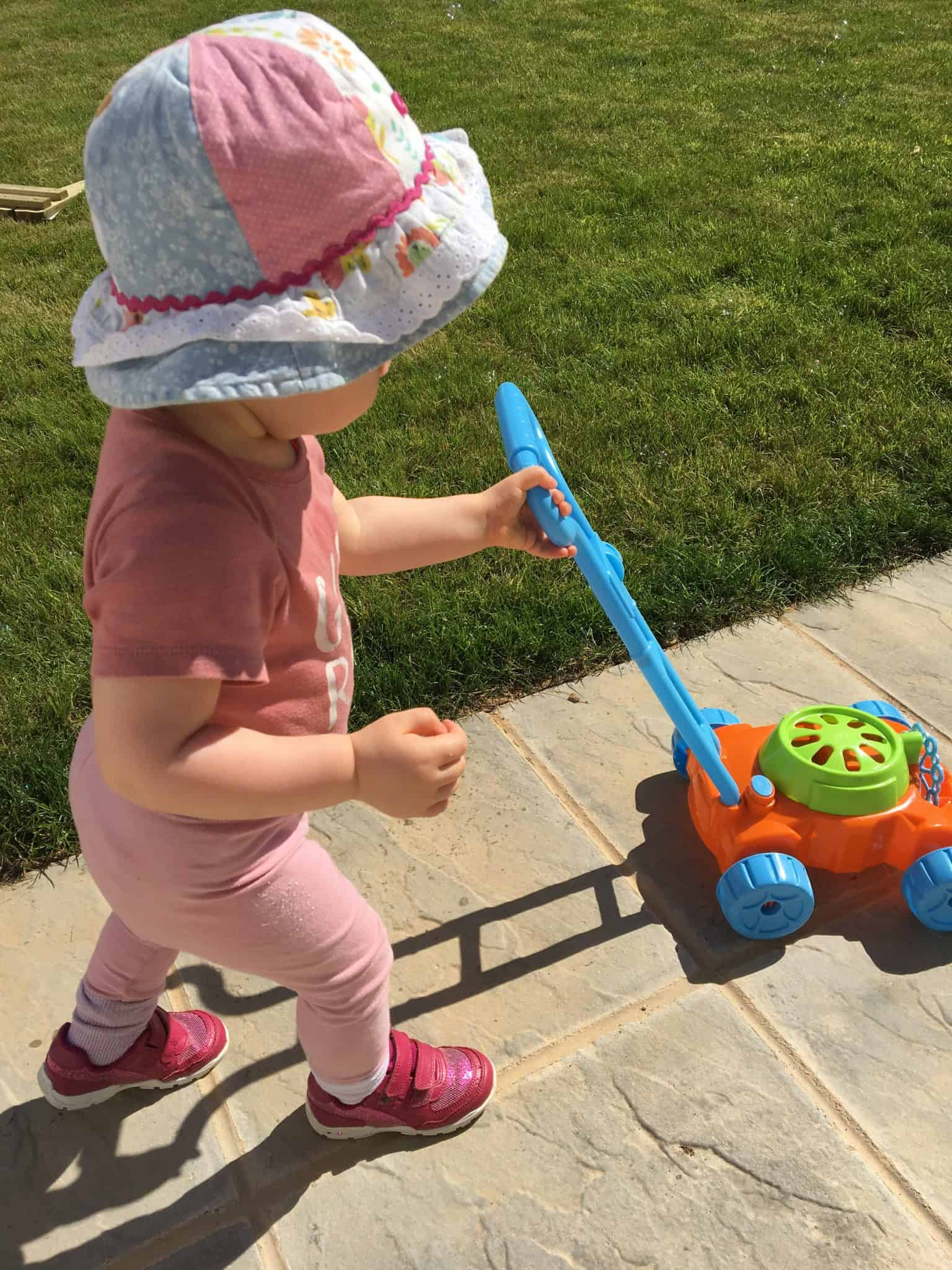 Baby girl playing outside in the sun