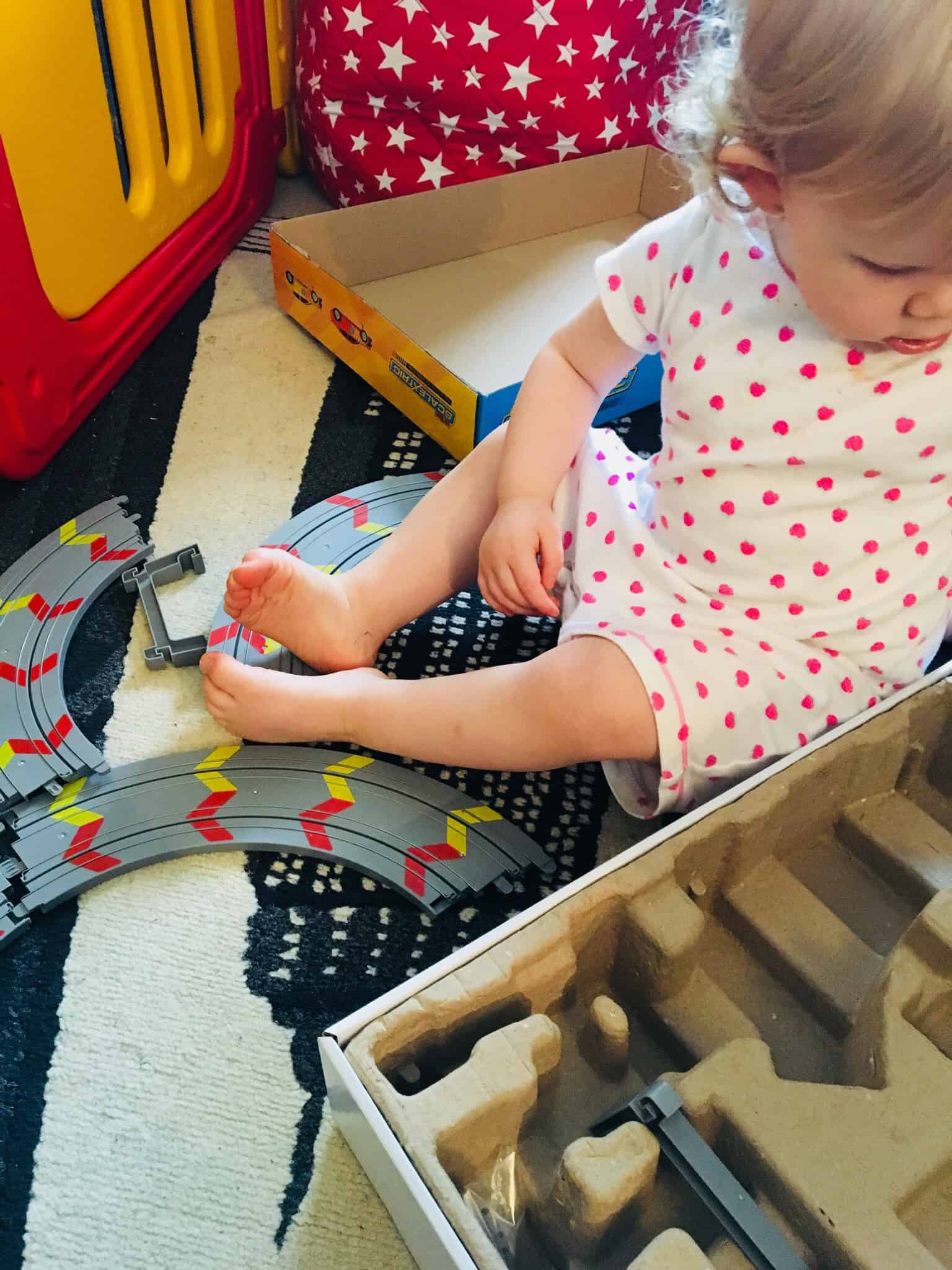 Baby girl opening up her My First Scalextric