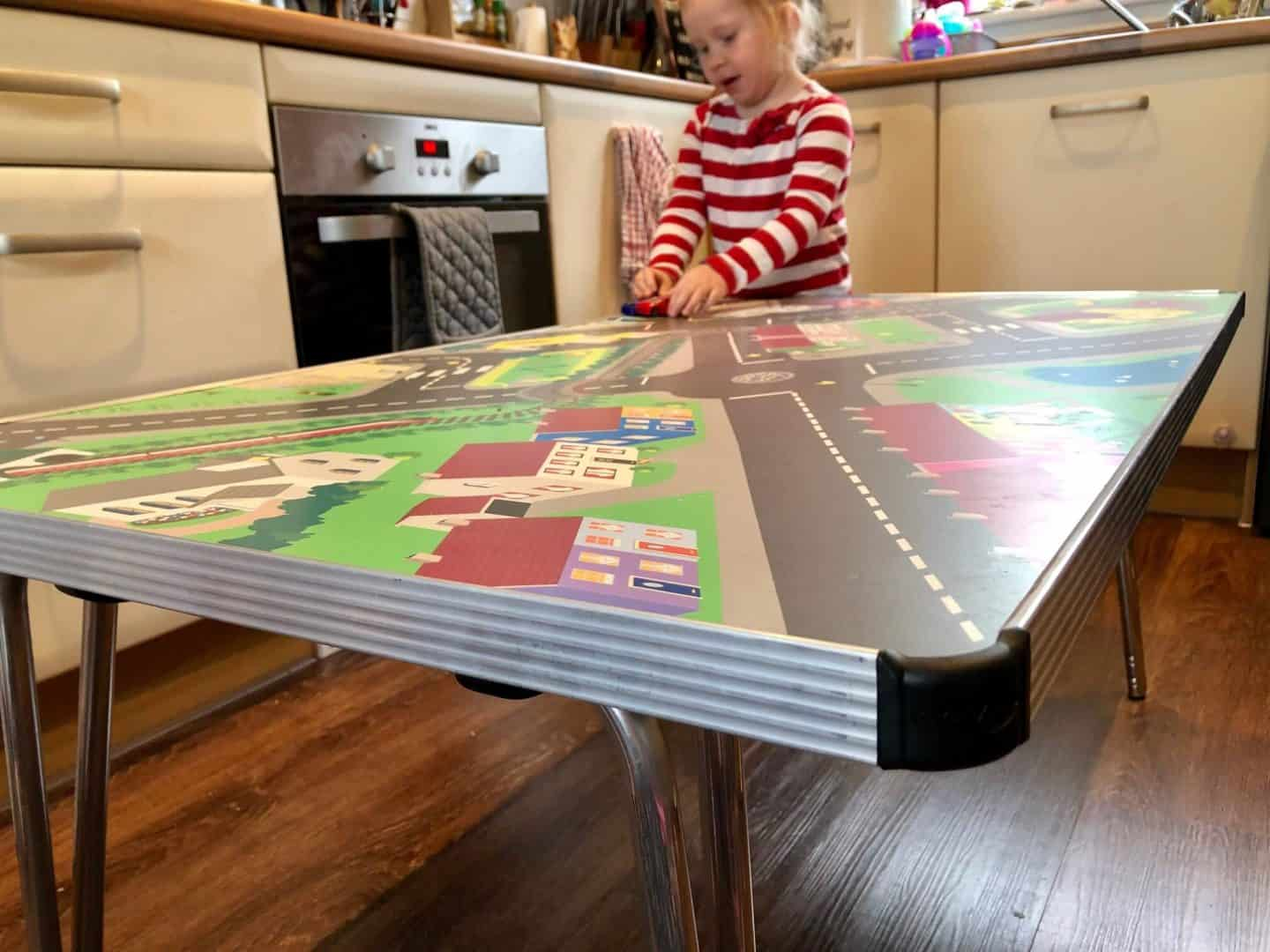 Playing with cars on the town activity table