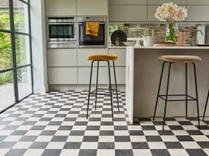 Cleaning Not letting dirt and spilt liquids to build upon your vinyl flooring in the kitchen is the best way for preventing any damage. You can do so by cleaning the floor regularly. Sweep the floors with a sweeping brush to remove grit, dirt, dust, crumbs and fallen hairs off of the floor. Opt for a cleaning solution sprayed on a mop for any spilt liquids or grease directly on the floor. When mopping the floor, avoid using too much liquid. Although vinyl flooring is liquid-resistant, it's still good practice not to drench the floor completely when mopping – it'll ensure the longevity of your kitchen floor. Long term care Vinyl flooring might resemble wooden flooring (depending on the type you have at home), but it does not require the same kind of attention as wood flooring. There is no wax polishing necessary as it can damage the topcoat of the vinyl. If you've got vinyl tiles in your kitchen and one of those gets damaged, you will probably be able to replace just that part of the flooring instead having to rip out the entire floor. However, always consult a specialist before doing any kind of installing or repairing. Lastly, make sure you use a special cleaning fluid that is made for cleaning vinyl floors. Especially stay away for any products containing bleach! To ensure your vinyl kitchen floors serve you a long time, a bit of care and maintenance is necessary. If you keep in mind the few tips provided in this post, you should be able to maintain beautiful floors in your kitchen with ease!