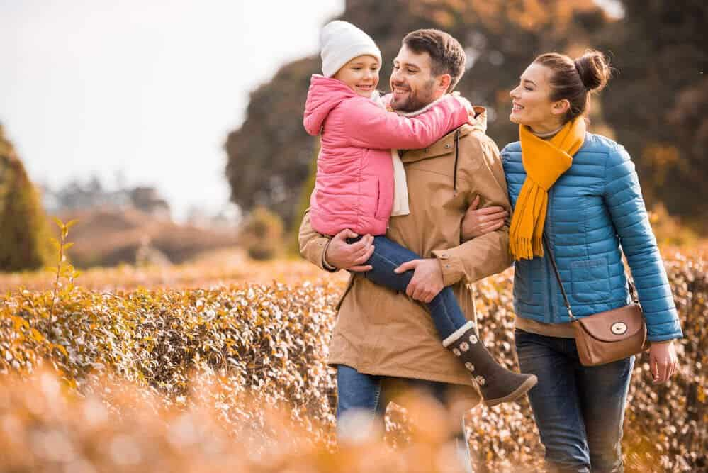 family walking through park - Simple Ways to Save Money for Your Family