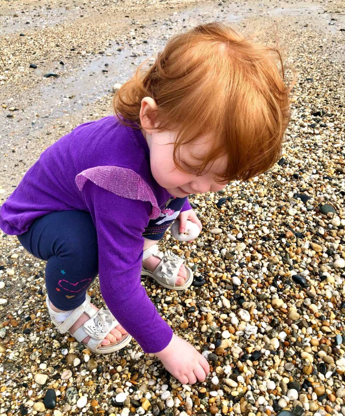 Little Dottie picking up pebbles at Marazion